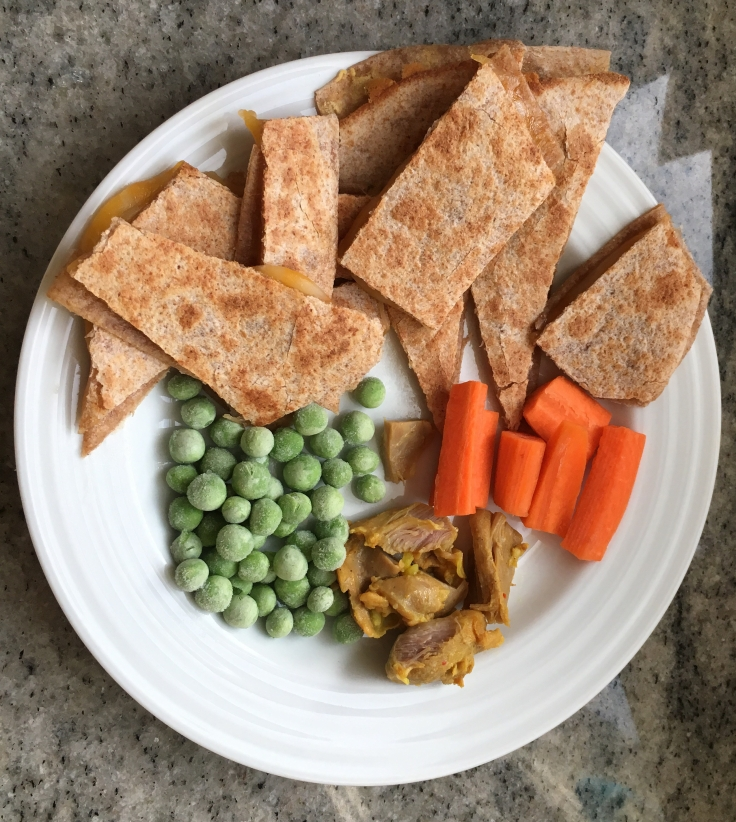 Kids quesadilla with chicken and veggies on the side.