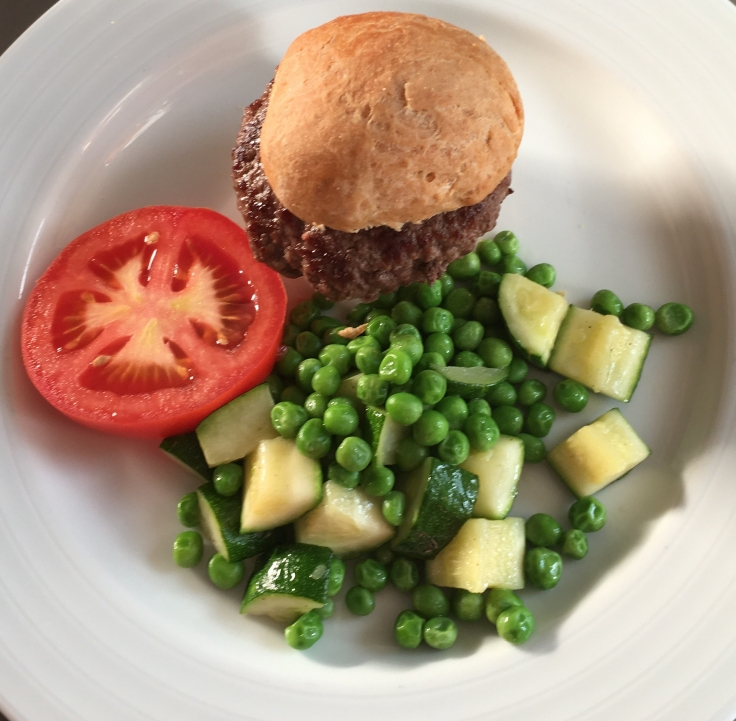 Beef burger on a wheat bun with Zucchini & Pea Salad